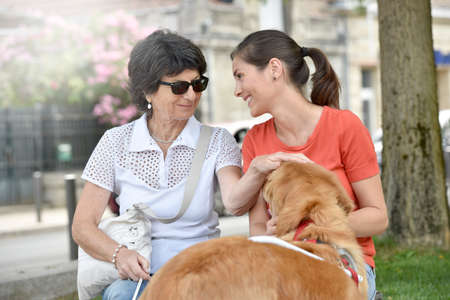 Blind woman and home carer relaxing on bench Stock Photo