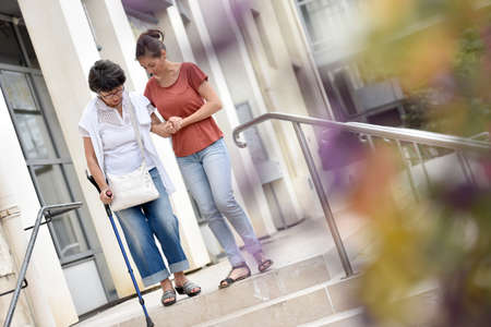 crutch: Home carer helping disabled woman getting down the stairs