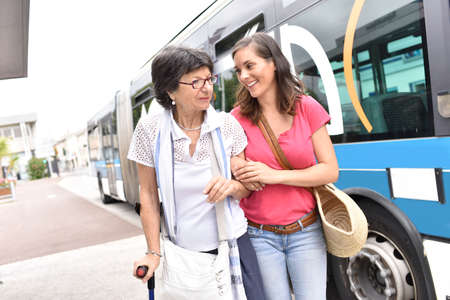 Hogere vrouw met thuis verzorger het afstappen van de bus