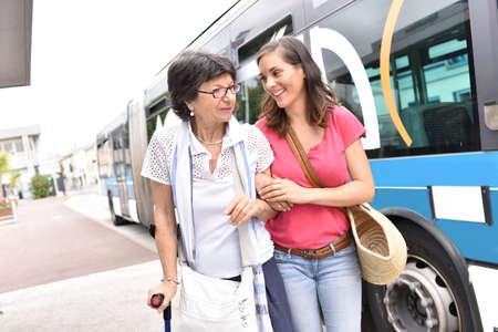 Mujer mayor con la cuidadora de la casa de bajar del autobús