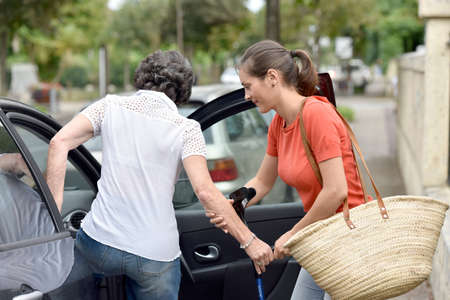 Young carer helping senior woman getting in car