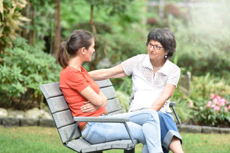 carer: Senior woman with carer sitting on bench at the park