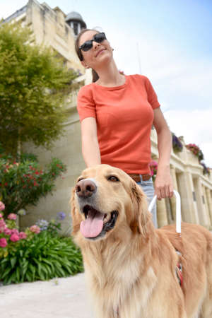 Blind woman petting her guide dog Stock Photo