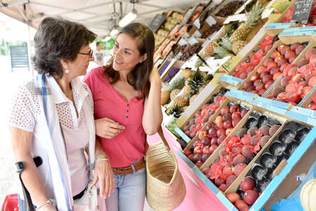 dependent: Senior woman going to grocery store with help of carer