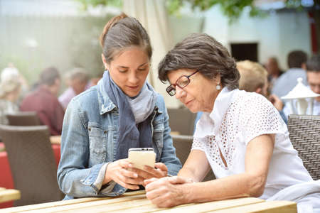 dependance: Senior woman and home carer at cafŽ terrace using smartphone