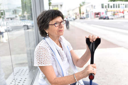 crutches: Senior woman with crutches waiting at bus stop Stock Photo