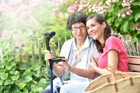carer: Senior woman with home carer sitting in park