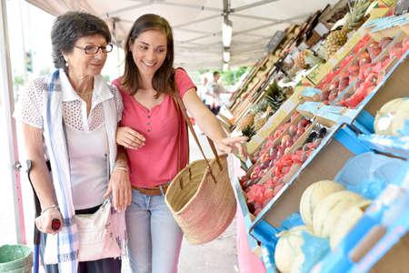 Senior vrouw die naar supermarkt met behulp van verzorger