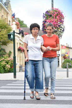 homecare: Home carer helping senior woman crossing the street