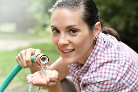 refreshment: Woman spreading water from garden hose Stock Photo