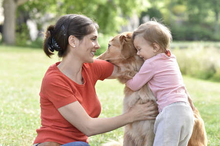 complicity: Woman and baby girl hugging golden retriever dog