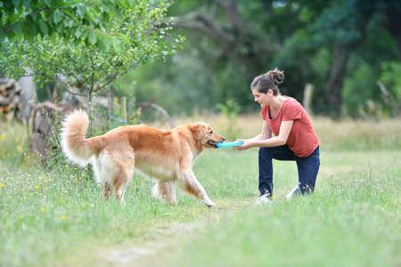 Mujer que juega con el disco volador que lanza al perro Foto de archivo - 62676758