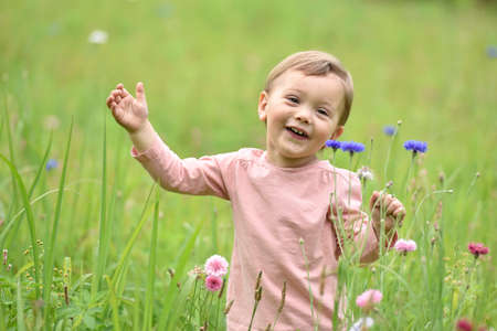 2 years old: Cute 2-year-old girl playing in wild flower field