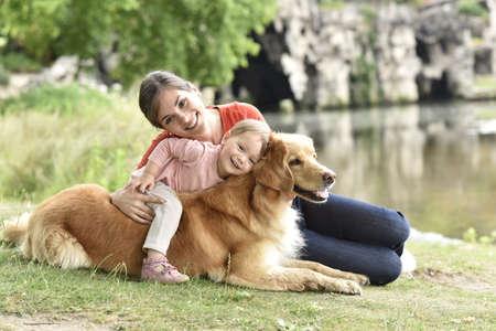 Vrouw en baby meisje spelen met golden retriever hond