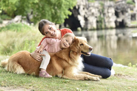 family playing: Woman and baby girl playing with golden retriever dog