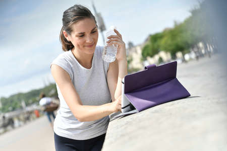 outdoor sport: Fitness girl looking at digital tablet for virtual lesson