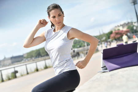 outdoor sport: Fitness girl in town exercising with virtual coach
