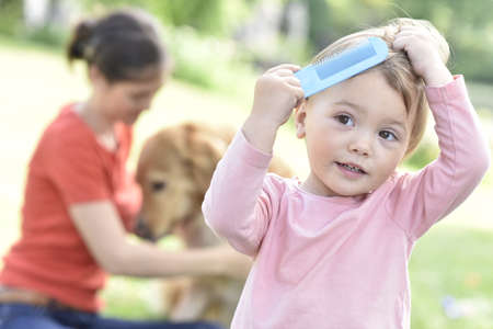comb: Baby girl trying to comb her hair Stock Photo