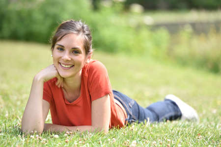 woman lying: Portrait of cheerful young woman laying in grass