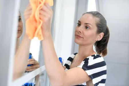 cleaning bathroom: Woman cleaning bathroom mirror