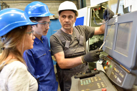 Metalworker with training people using electronic machine Banco de Imagens