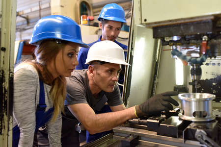 trainees: Metal worker teaching trainees on machine use
