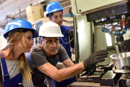 metal worker: Metal worker teaching trainees on machine use
