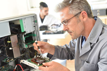 harddrive: Electrical technician fixing computer hard-drive