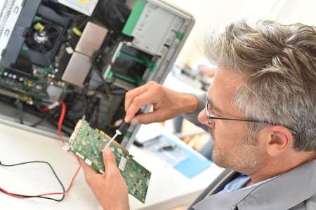 electricista: Electrical technician fixing computer hard-drive