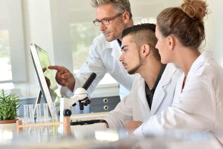 Studenter i biologi som deltar i träning med mikrobiolog
