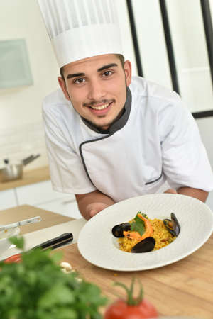 gastronomy: Young chef in cooking training school presenting dish