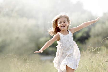 blond girl: Little girl running in country field in summer