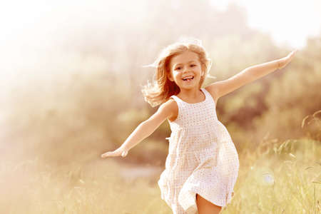 Little girl running in country field in summer