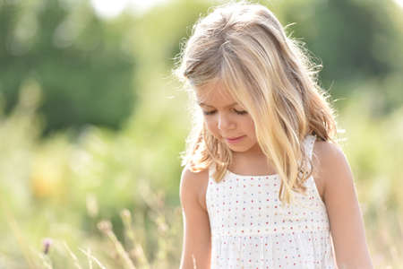 airiness: Portrait of cute little blond girl in countryside, summertime