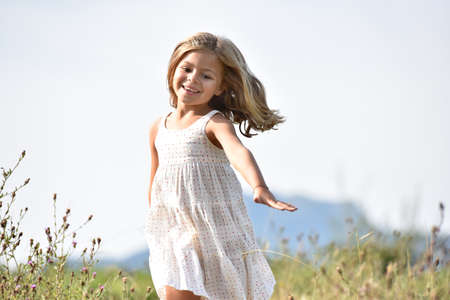 airiness: Little girl running in country field in summer