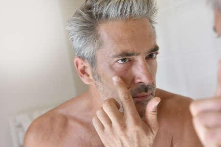 mature man: Mature man in front of mirror applying cream