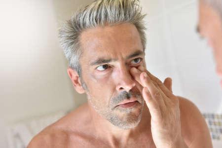 hombres maduros: Hombre maduro en frente del espejo de aplicar la crema Foto de archivo