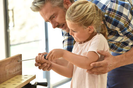 Daddy teaching daughter how to use screwdriver Stock Photo