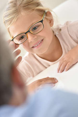 doctor of optometry: Little girl at the optician trying different eyeglasses
