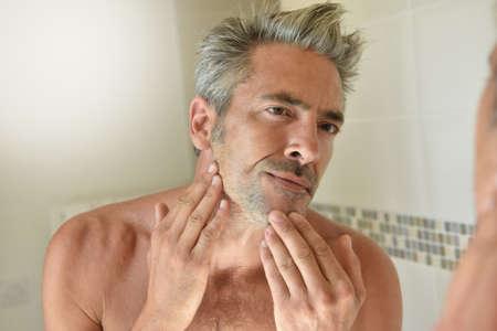 mature man: Mature man in bathroom checking beard