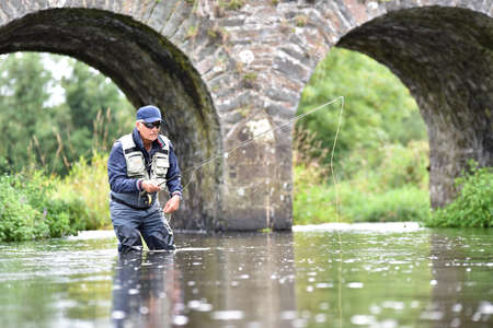 fly: Fly fisherman fishing in river to catch brown trout Stock Photo