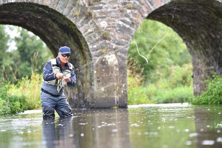 Pêche à la mouche de pêcheur dans la rivière pour attraper la truite brune