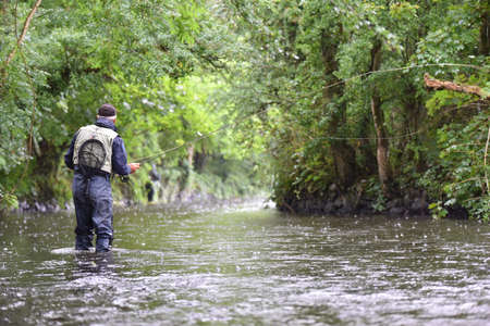 waders: Back view of fly-fisherman fishing in river