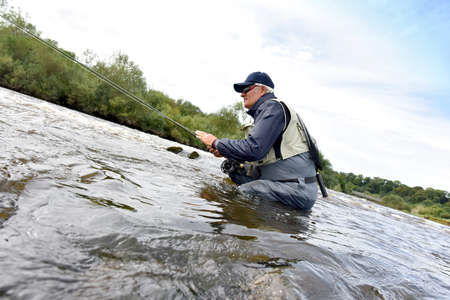 botas altas: Fly fisherman fishing in river to catch brown trout Foto de archivo