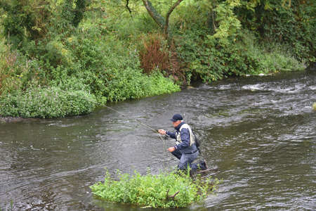 waders: Upper view of fly fisherman fishing in river Stock Photo