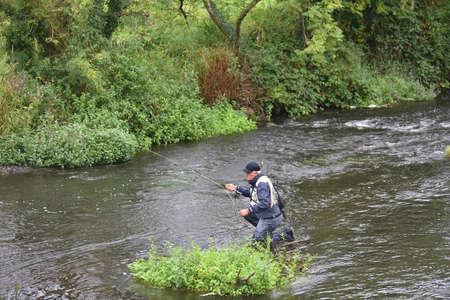 botas altas: Upper view of fly fisherman fishing in river Foto de archivo