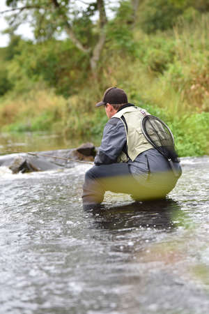 knelt: Fly-fisherman fishing in river Stock Photo
