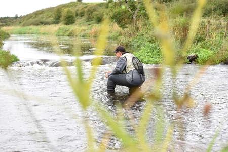 botas altas: Back view of fly-fisherman fishing in river
