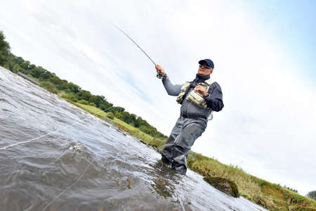 waders: Fly fisherman fishing in river to catch brown trout Stock Photo