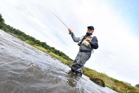 botas altas: La pesca con mosca pescador en río para coger la trucha marrón